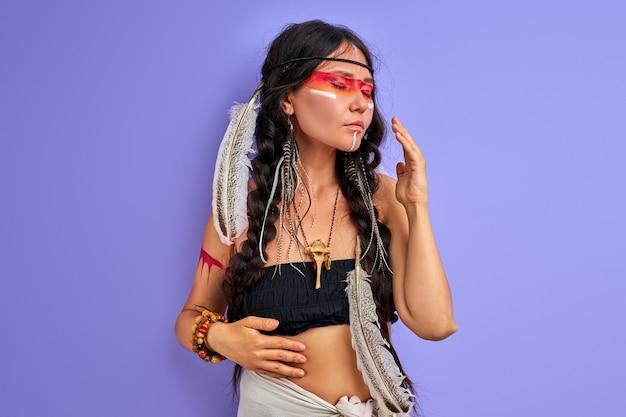 髪にインドの羽とカラフルなペイントメイク、スタジオでの肖像画を持つシャーマニズムの女性。インドの民族性