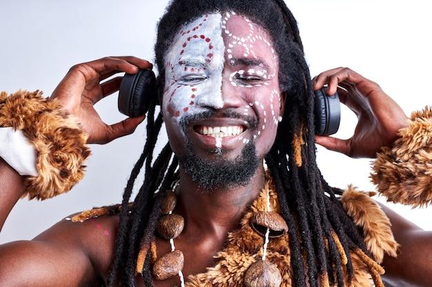 Shamanic male using headphones, holding it near ears, enjoying music with closed eyes, isolated over white wall