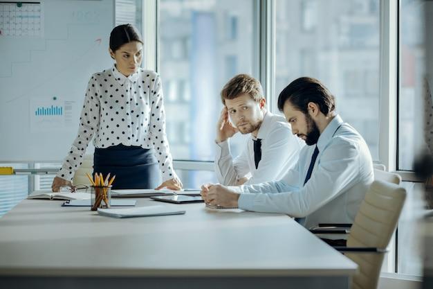 恥を知れ。厳格な若い女性の上司が彼女の従業員に眉をひそめ、彼らが有罪に見えて視線をそらしている間、彼女のオフィスで彼らを叱る