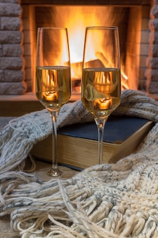 Shampagne glasses, opened book and wool scarf against cozy firepace.