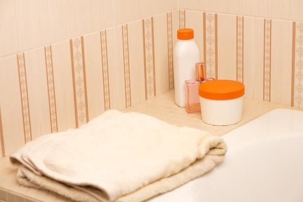 バスルームにシャンプー、ボディバター、ヘアオイル、バスタオル。テキスト用のスペース