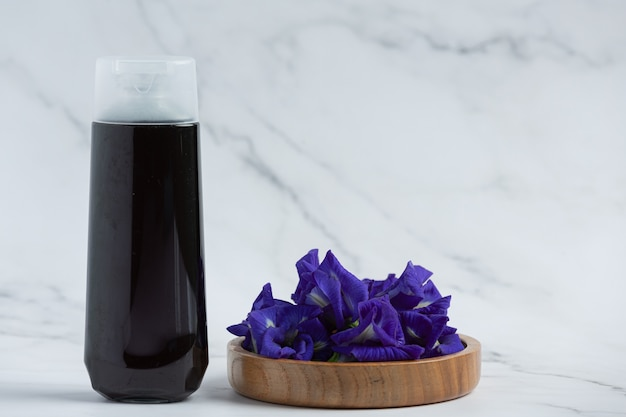 Shampoo bottle of butterfly pea flower put on white marble background
