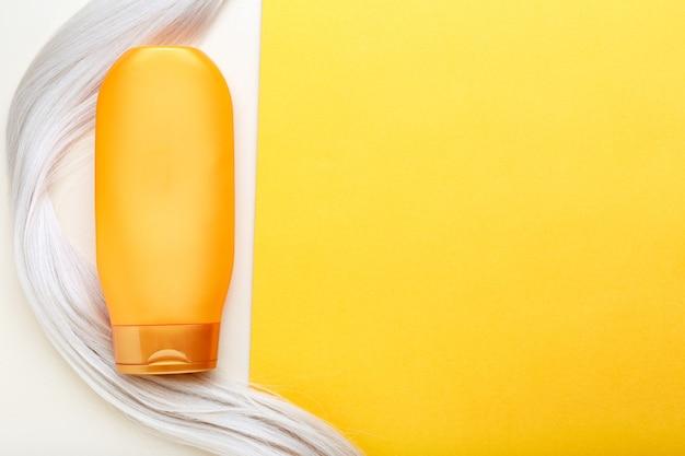 オレンジ色の背景にブロンドの髪のロックカールのシャンプーボトルモックアップストランド。上面図のコピースペース。