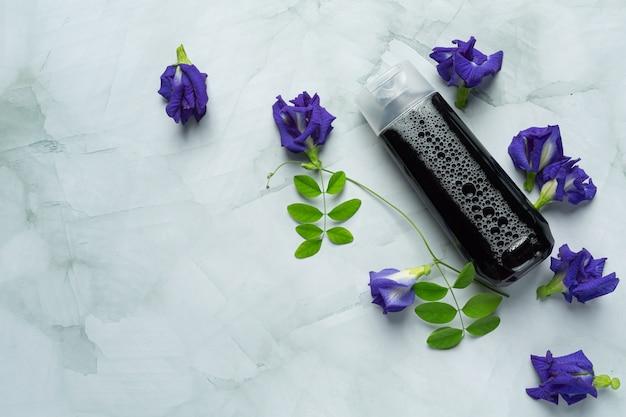 白い大理石の背景に置かれた蝶エンドウ豆の花のシャンプーボトル