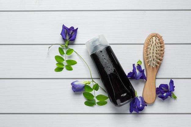 白い木製の背景に置かれた蝶エンドウ豆の花のシャンプーボトル