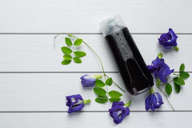 Бутылка шампуня butterfly pea flower на белом деревянном фоне