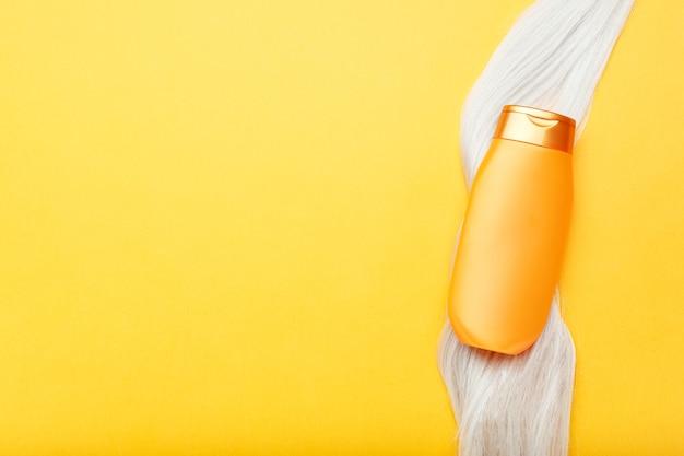 オレンジ色の背景にブロンドの髪のロックのシャンプーボトル。染めた髪の毛のゴールドボトルシャンプー。