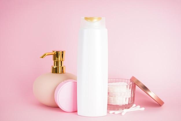 Бутылка шампуня, дозатор мыла на розовом фоне.