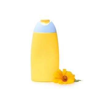 Бутылка шампуня с цветком календулы, изолированные на белом фоне. экстракт календулы.
