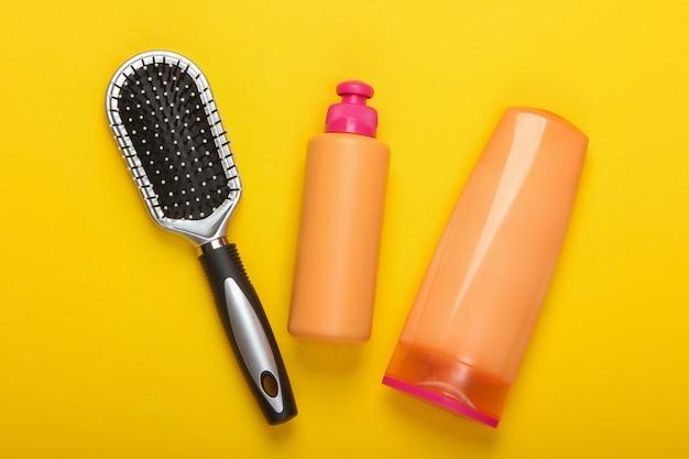 Бутылки шампуня, кондиционер для волос, щетки для волос на розовом. уход за волосами. гигиена