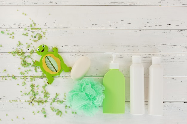 Shampoo bottles on wooden table. baby bath accessories. child toilet stuff. bathroom tubes, balm, sea salt, soap.