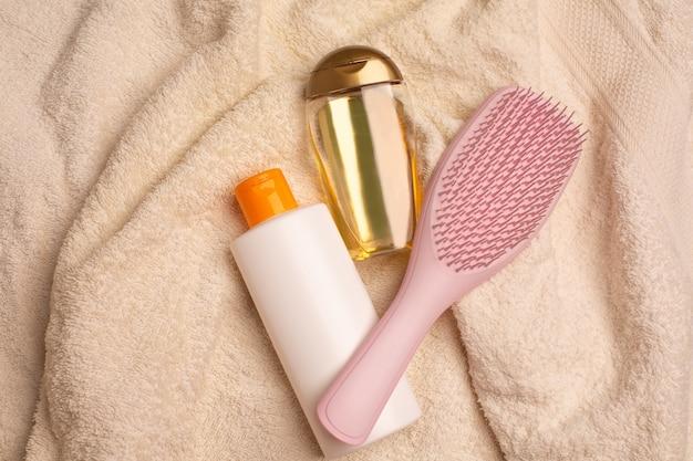 バスルームのしわくちゃのタオルの上に横たわるシャンプー、くし、活力を与えるヘアオイル。コピースペース