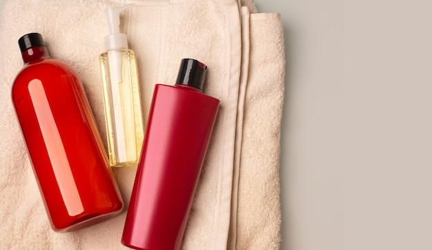 バスルームのバスタオルの上に横たわるシャンプー、コンディショナー、クレンジングオイル。テキスト用のスペース