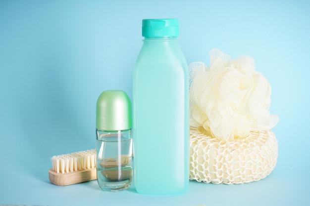 Шампунь, дезодорант и мочалка на синем фоне.