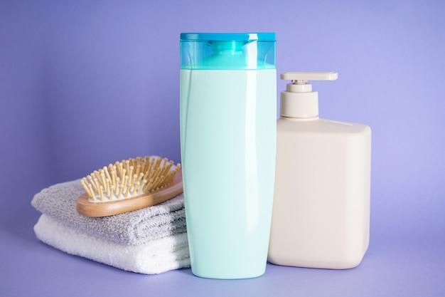 Шампунь, щетка для волос и полотенце на фиолетовом фоне.