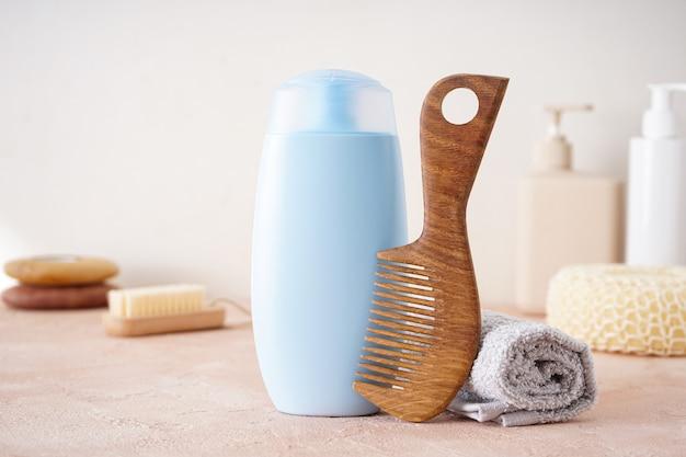 Shampoo, hair brush, towel and washcloths on a beige background.