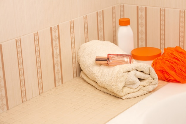 Shampoo, hair conditioner, body oil and bath towel in a bathroom. space for text