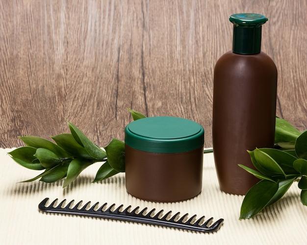 シャンプー、ヘアマスク、コームと新緑の葉。コピースペースのあるナチュラルヘアケア化粧品
