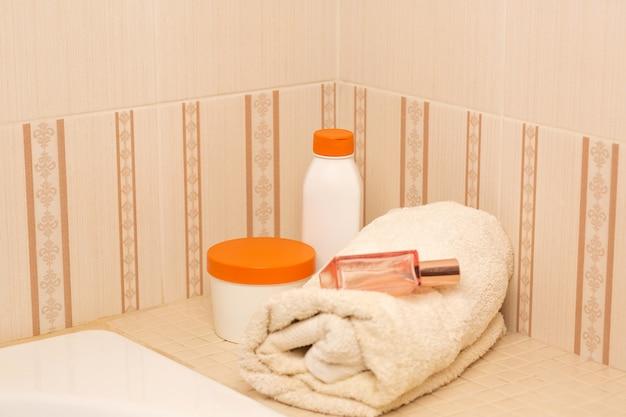 バスルームにシャンプー、ヘアマスク、ボディオイル、バスタオル。テキスト用のスペース
