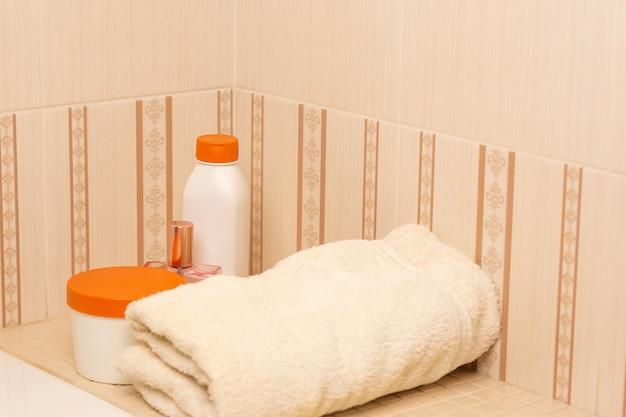 バスルームにシャンプー、ヘアトリートメントマスク、ボディオイル、バスタオル