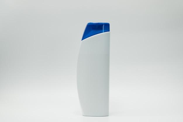空白のラベルとコピースペースで白い背景に分離された青いディスペンサーポンプ付きシャンプーまたはコンディショナーボトル。シャンプーやコンディショナーの宣伝に使用します。化粧品パッケージ。美容製品