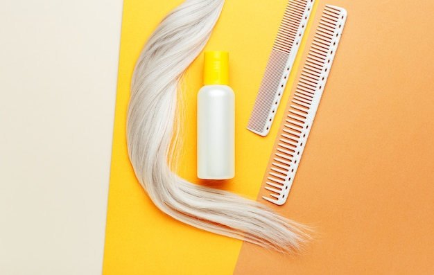 Оранжевая бутылка шампуня с прядью локонов светлых волос и расчески. парикмахерские инструменты, парикмахерское оборудование для парикмахерских