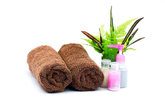 Shampoo and shower gel bottles and brown towel on white background