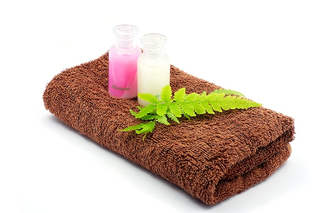 Shampoo and shower gel bottles and brown towel on white background.