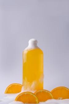 シャンプー、シャワージェル、オレンジ色のピースと泡の明るい背景の透明なボトルに天然成分を含むオレンジ色の液体石鹸