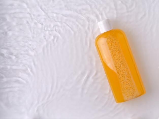 シャンプー、シャワージェル、水に明るい背景の透明なボトルに天然成分を含むオレンジ色の液体石鹸