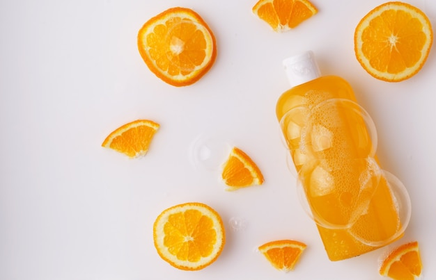シャンプー、シャワージェル、泡とオレンジスライスの明るい背景の透明なボトルに天然成分を含むオレンジ色の液体石鹸