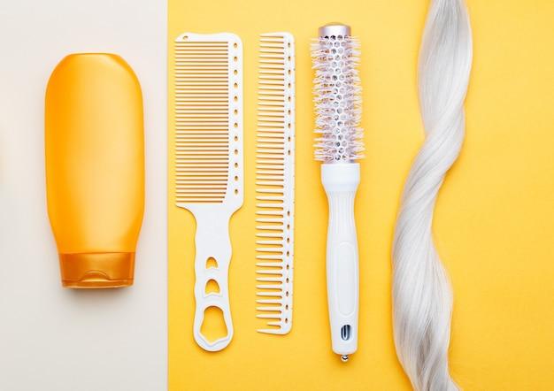 Шампунь, прядь светлых волос, разные расчески на цветном фоне