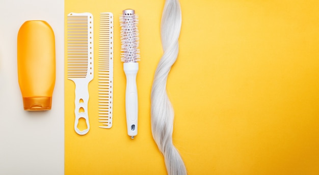 Шампунь, прядь светлых волос, разные расчески на цветном фоне. окрашенные окрашенные волосы, уход за волосами, услуги салона красоты парикмахерская. длинный веб-баннер с местом для текста.