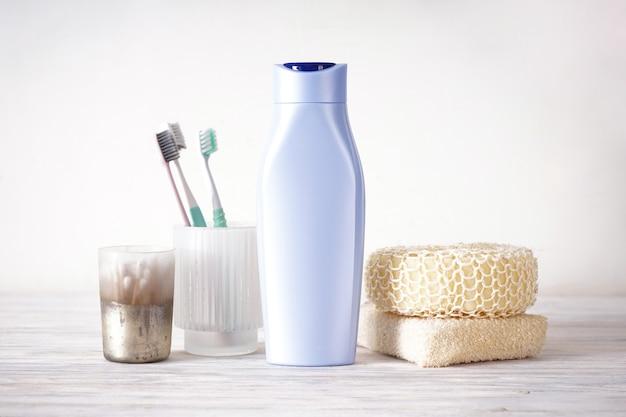 Шампунь, мочалки и зубные щетки на деревянном столе в ванной комнате.