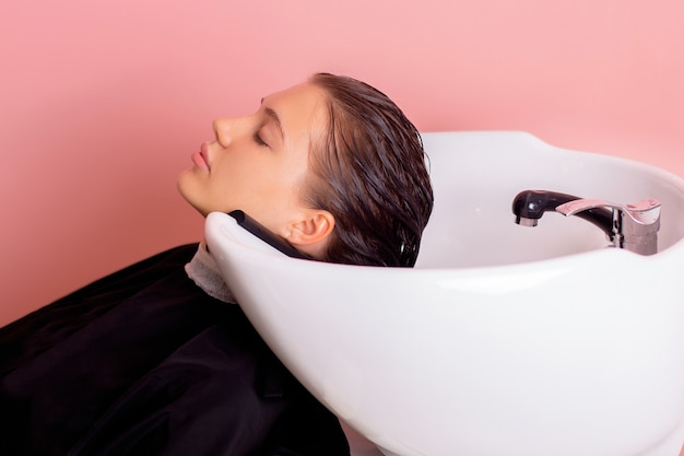 Shampoo washing of female head with long brunette hair in hairdressing salon