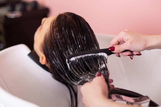 Мытье шампуня женской головы с длинными волосами брюнетки в парикмахерской
