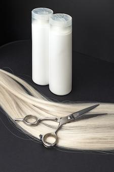 Shampoo white bottles, professional hairdresser scissors on strand of blonde hair