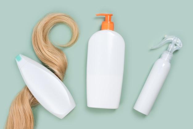 Шампунь, завернутый в прядь вьющихся светлых волос, бутылку с кондиционером и макеты лака для волос на мятном фоне, вид сверху. квартира выложена в пастельных тонах. косметика по уходу за волосами, средства по уходу за волосами, уход за волосами.