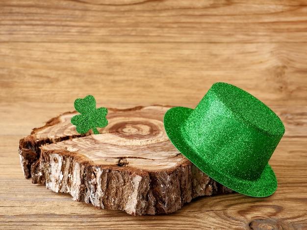 나무 테이블에 토끼풀 클로버와 녹색 모자, 성 패트릭의 날 아일랜드 휴일의 상징