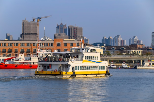Шанхай, китай - 18 февраля 2021 года: река хуанпу в шанхае, китай, с грузовым судном, перевозящим товары. на заднем плане - современные небоскребы бунда.