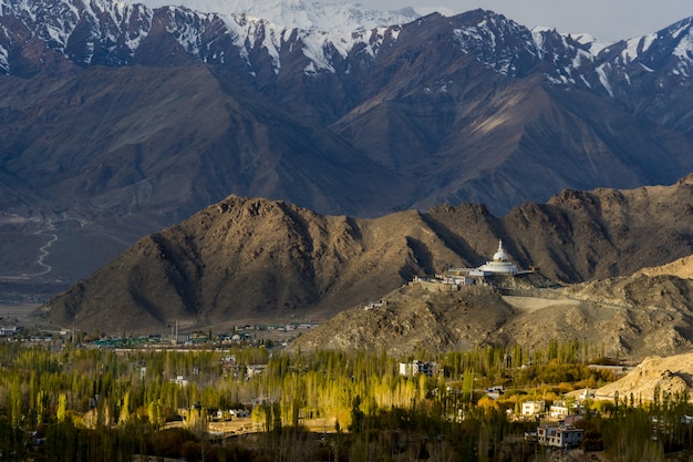 Shanti stupa with the big mountain in background and leh city with golden leaf in autumn