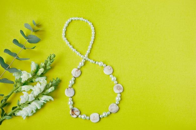 白い花が付いている紙の上の8つの8の数字の形の図国際女性の日カード春