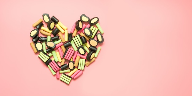 Shape of heart. colorful lollipop and licorice candy on pink.