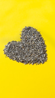 Shape of heart from chia seeds on yellow background. simple flat lay with pastel texture.