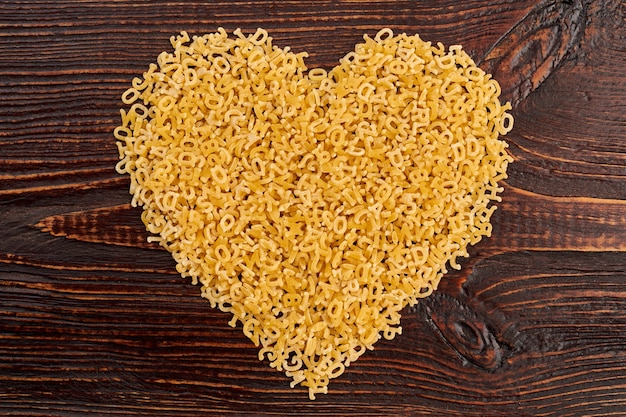 Shape of heart from italian stelline pasta. little macaroni letters forming heart shape. happy valentines day.