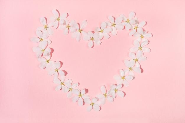 Сердце формы выложено из цветов белой яблони на розовом фоне.