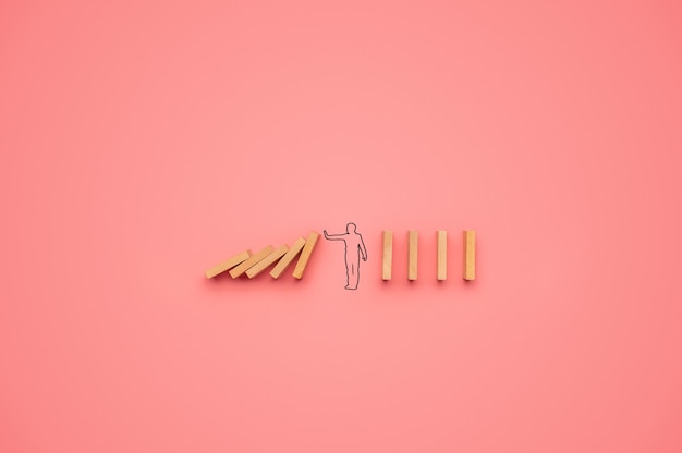 Shape of a man stopping dominos from falling in a conceptual image. over pink background.