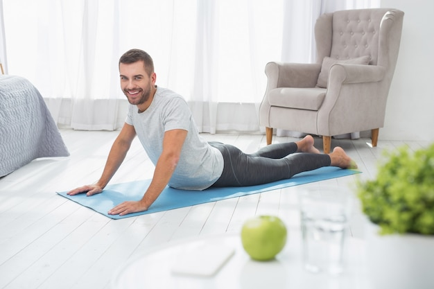 In shape. nice joyful man lying on the floor while doing push ups