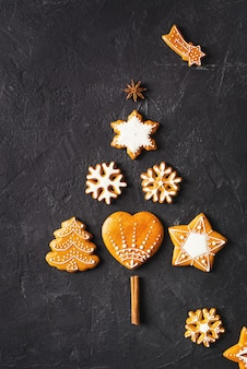 黒の背景にジンジャーブレッドのモミの形、クリスマスと新年あけましておめでとうございますのコンセプト、コピースペース上面図、垂直