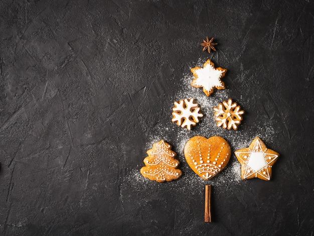 黒の背景にジンジャーブレッドのモミの形、クリスマスと新年あけましておめでとうございますのコンセプト、コピースペース上面図、